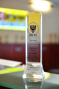 Statuetka DCG na tle logo firmy